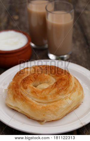 Traditional Bulgarian pastry Banitsa on a rustic table with Greek yogurt and juice