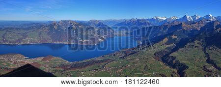 Landscape in the Bernese Oberland. Lake Thunersee. Distant view of Eiger Monch and Jungfrau. Villages Spiez Aeschi and Aeschiried. Shadow of mount Niesen.
