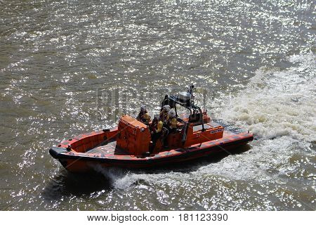 London, March 2017 - A motor launch operated by the Royal National Lifeboat Institution, a UK charity operating lifeboats, speeds down the River Thames