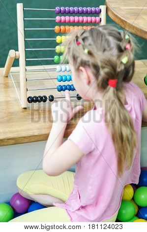 A little girl with her finger counts on colored wooden abacus sitting with her back to the camera