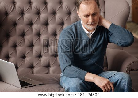 I need gymnastics. Portrait of sold handsome man touching his aching neck while sitting on couch at home.