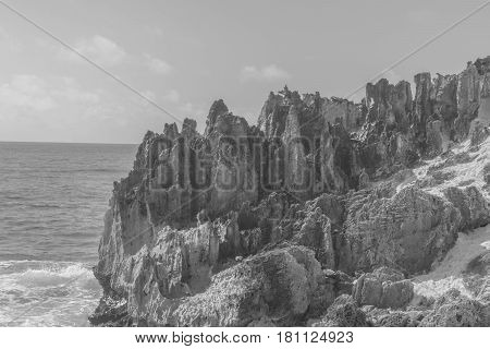 Jagged Structures: a black and white shot of jagged Stone Formations on the coastline, with ocean water