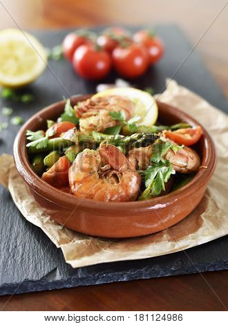 Fresh jumbo shrimps and green asparagus, delicious dish or meal, close-up shot. Spanish Tapas.