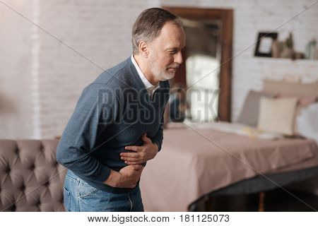 Terrible toxication. Side view of old man having strong stomach-ache while standing at home.