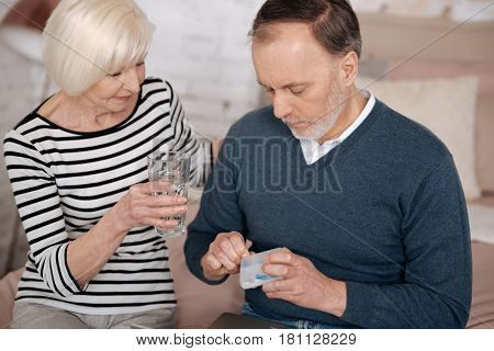 With love. Senior man is taking out some pills from case while his wife holding water glass for him.