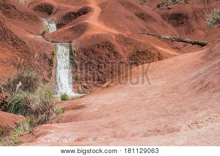 Red Sand Waterfall: a small, cascading waterfall set among rolling red mounds