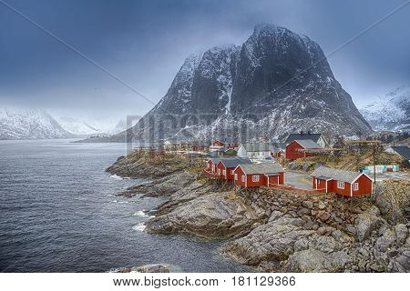 Travel Concepts and Ideas. Traditional Fishing Hut Village in Hamnoy Mountain Peak in Lofoten Islands Norway. Horizontal Image Composition