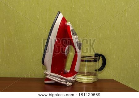 Iron red for ironing clothes on a brown table against a green wall.