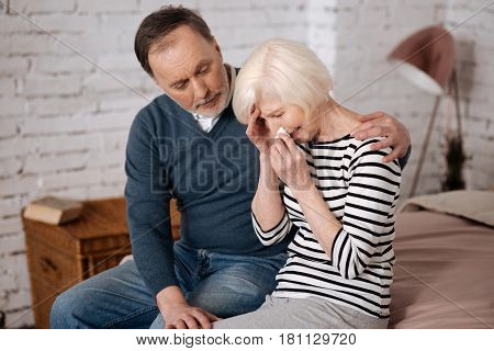 So bad news. Senior lady is crying while sitting near her husband, that is giving her support.