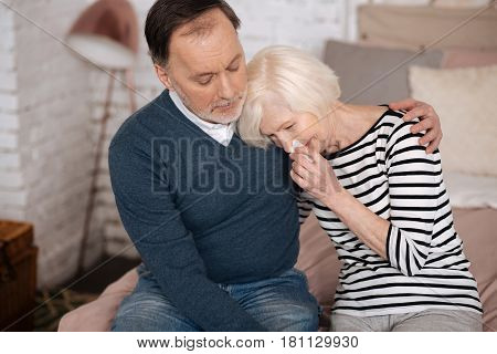 Tell me why. Very sad senior lady is crying and leaning on shoulder of her husband.