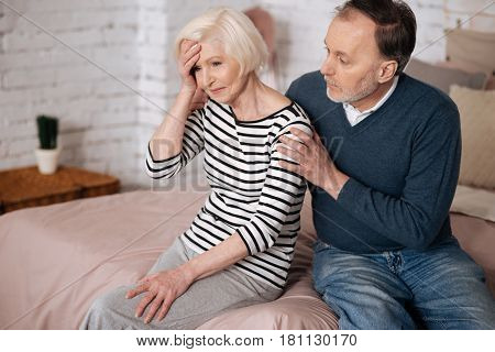 Do not panic. Old frustrated woman is sitting on bed near her husband and touching her forehead with hand.