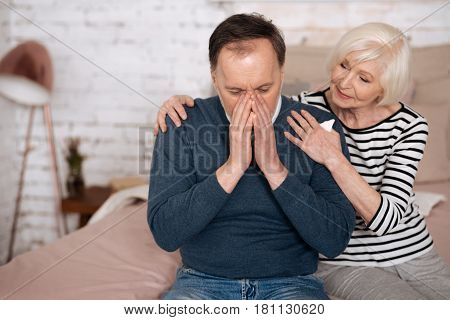 Bad allergy. Old man is covering his face while sneezing and his senior wife supporting him.