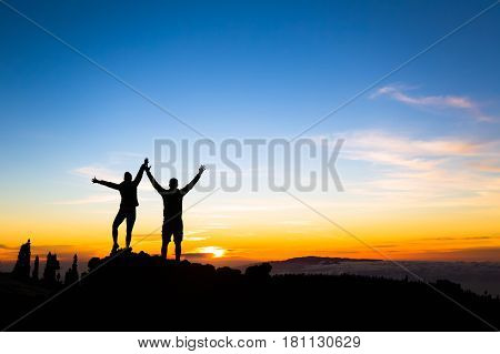 Couple hikers success in sunset mountains accomplished with arms up outstretched. Man and woman on rocky mountain looking at beautiful sunset inspirational landscape view Tenerife Canary Islands.