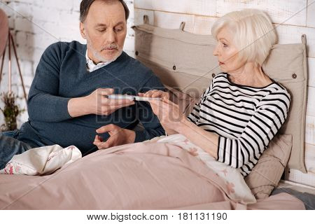 It will help. Senior handsome man is giving pills case to his elderly sick wife lying on bed covered with warm blanket.