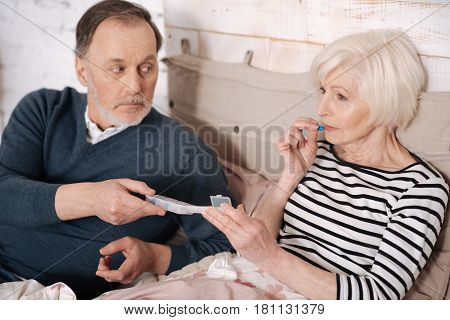 For recovering. Close up of old ill woman taking pill from case held by her elderly husband.