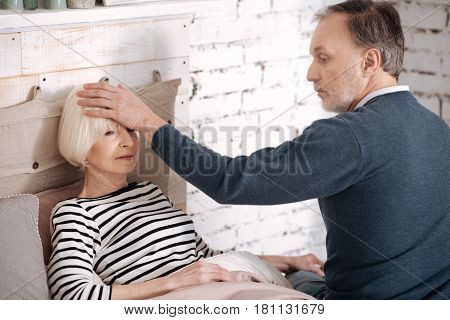 You have fever. Handsome senior man touching forehead of his lying wife in order to feel fever.