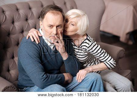 Let me help. Pretty elderly woman is kissing her poor husband having terrible toothache.