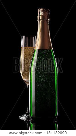 Glass and bottle of champagne on a black background