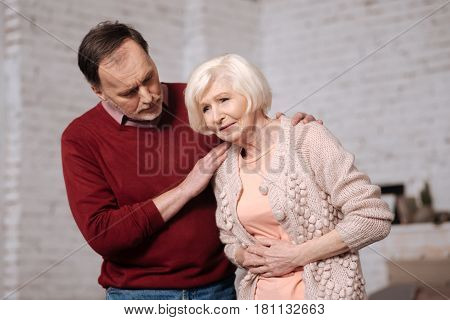 Bad sushi. Aged woman leaning and touching her tammy because of stomachache while her husband supporting her.
