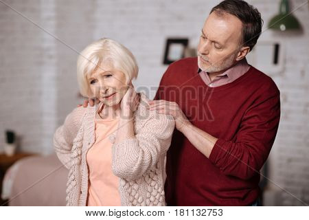 Feeling spasm. Pretty elderly woman standing and touching her aching neck while her husband supporting her.