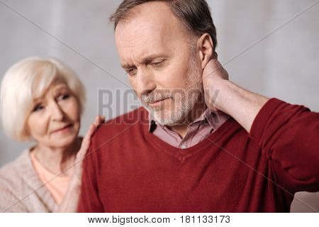 So painful. Close-up portrait of elderly man touching his aching neck while his wife trying to support him.