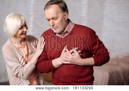 So sudden. Portrait of aged man with heartache standing and touching his heart area while his wife supporting him.