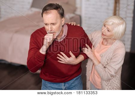 Bronchitis again. Senior man standing and strongly coughing while his wife is giving him support.