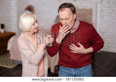 Drink some water. Elderly sick man standing and coughing strongly while his loving wife offering him water glass.
