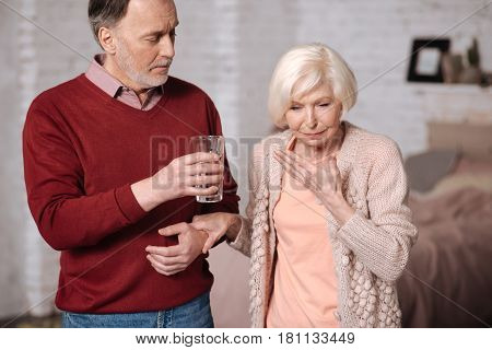Water will help. Senior lady feeling very bad and her husband proposing her some water.