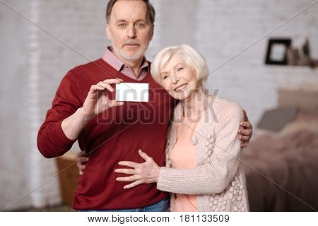 We are insured. Pretty elderly woman embrasing her husband holding while social security card.