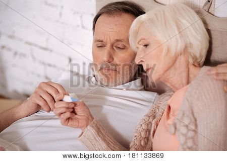 Are we ill. Close up portrait of elderly couple lying on bed and looking on thermometer in order to check temperature.