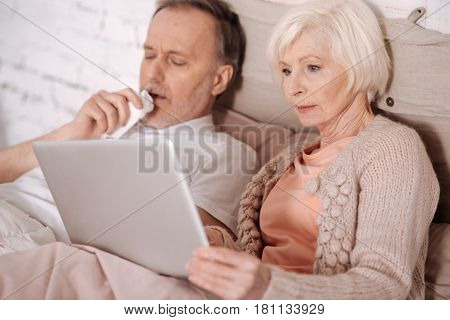 Trying to entertain. Elderly woman lying on bed near her coughing husband and holding laptop.