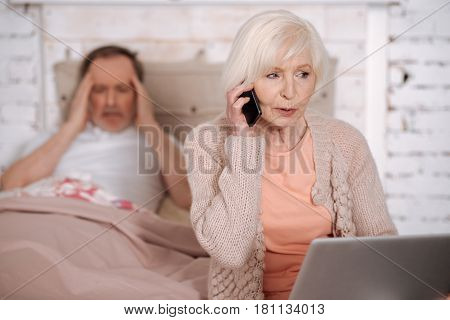 Hurry up. Senior woman calling emergency while sitting on bed holding laptop near her ill husband with terrible headache.