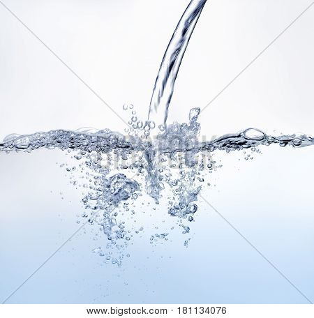 Water jet splashing against water surface. Blue color on white background