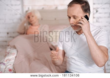 Please hurry up. Portrait of elderly man calling emergency while his ill wife lying on ben with terrible headache.