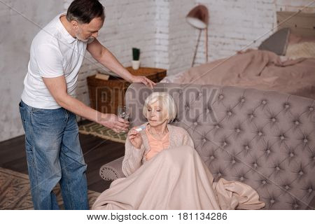 Drink it. Aged ill woman sitting on couch covered with warm blanket and holding thermometer while her husband serving her water glass.