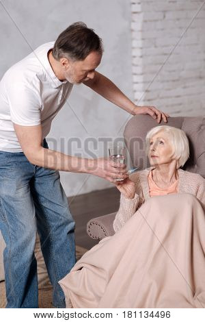 Take it. Close up of elderly man leaning to his aged wife with glass.