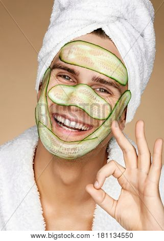 Funny man receiving facial mask of cucumber and showing okay gesture. Cosmetic procedure man's face. Grooming himself
