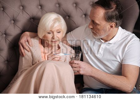 Oh no. Sad aged woman sitting covered with warm blanket near her loving husband holding water glass and checking thermometer.