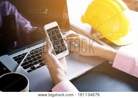 Hi tech engineer using smartphone for construction industry