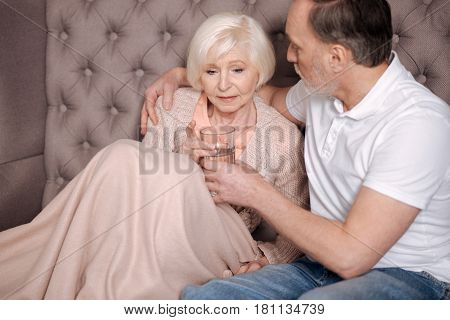 Drink some water. Portrait of worried elderly lady sitting covered with warm blanket and holding water glass near her supporting husband.