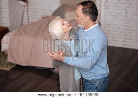 I love you. Top view of aged man and woman standing and dancing together while looking at each other at home.