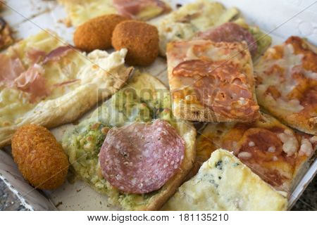 assortment of various types of pizza cut in pieces and stuffed arancine