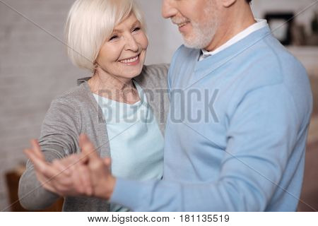 I love him. Close up portrait of happy aged woman smiling while dancing with her husband.