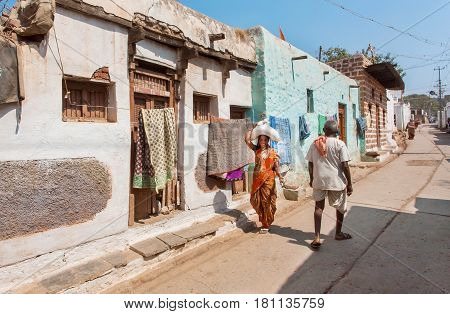 BADAMI, INDIA - FEB 8, 2017: Narrow street of poor indian town with some people walking at hot day in Karnataka state on February 8, 2017. Population of Karnataka is 62000000 people