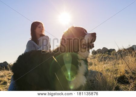 Woman with her pet contemplates the sunset from the top of the hill