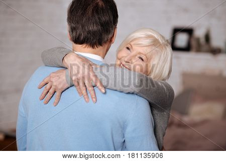 With love. Portrait of happy elderly lady embracing her loving husband at home.