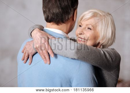 With great love. Close-up portrait of beautiful smiling elderly woman embracing her husband.