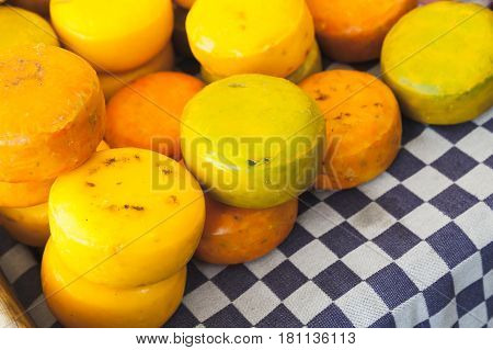 Heads Of Dutch Cheese Lay On Checkered Tablecloth