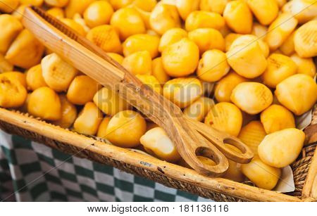 Small Heads Of Smoked Cheese With Wooden Tongs